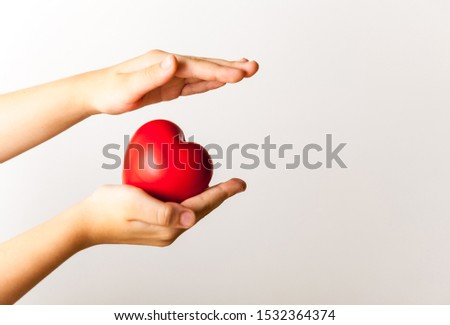 Life in your hands - red heart in child's hands on light background. Medical and health care concept #1532364374