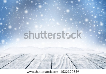 Decorative winter Christmas background with bokeh lights, snowflakes and empty old wooden table. Christmas and Happy New Year blue background with snowflake. Winter landscape with falling snow. #1532370359