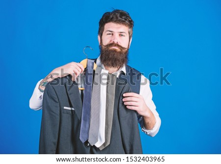 Guy choosing necktie. Perfect necktie. Shopping concept. Shop assistant or personal stylist service. Stylist advice. Matching necktie with outfit. Man bearded hipster hold neckties and formal suit. #1532403965