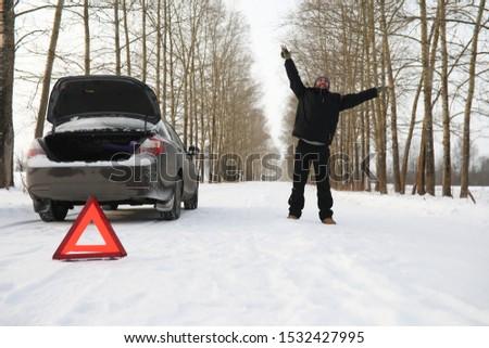 Man and car. Winter road walk and car repair.