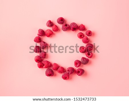 Creative layout with fresh ripe berries. Raspberry on pink background with round empty circle in center for copy space. Can use for your design. Top view or flat lay. Negative space for text
