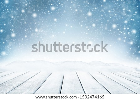 Decorative Christmas background with bokeh lights, snowflakes and empty old wooden table. Christmas and Happy New Year blue background with snowflake. Winter landscape with falling snow. #1532474165