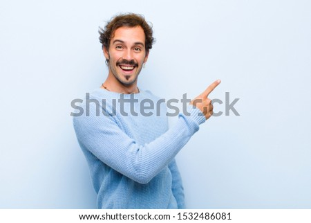 young handsome man looking excited and surprised pointing to the side and upwards to copy space isolated against flat wall #1532486081
