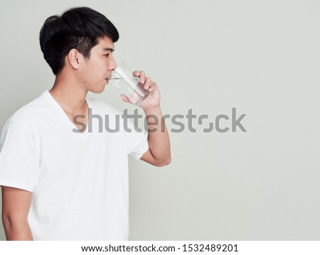 Studio portrait of young asian man drinking water on white background. #1532489201