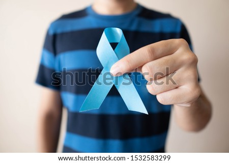 Men's health and Prostate cancer awareness campaign in November month. Close up of young man hands holding light blue ribbon awareness. Symbol for support men who living with cancer. #1532583299