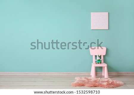 Chair with toy near color wall in children's room