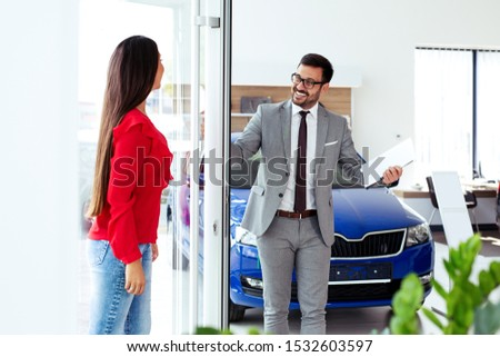 Salesperson showing vehicle to potential customer in dealership #1532603597