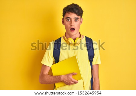 Teenager boy wearing headphones and backpack reading a book over isolated background scared in shock with a surprise face, afraid and excited with fear expression #1532645954