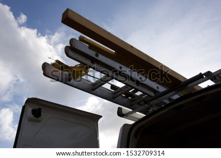 Ladders: access ladders and timber strapped to the roof rack of a roofer's van #1532709314