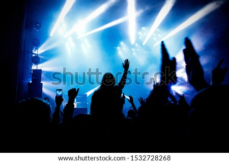 The audience at the concert enjoys. Silhouettes of raised hands and smartphones #1532728268
