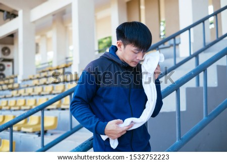 Sport man leaning againt the grandstand's handrail and wipe his sweat. #1532752223