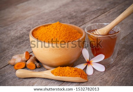 Turmeric ( curcumin, Curcuma longa Linn) powder in wooden bowl and scoop with rhizome and glass of honey isolated on old wood table background. Beauty and spa concept. #1532782013