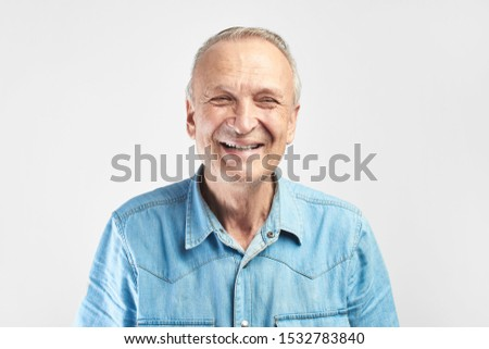 Portrait of a Caucasian elderly man smiling on a white studio background. Handsome gray-haired old pensioner with a friendly kind face #1532783840