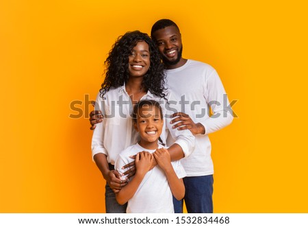 Happy Family Of Three Hugging Posing Over Yellow Background In Studio