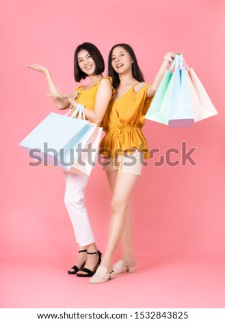 Asian pretty young woman sitting on pink  pastel background. She smiling and  happy shopping bags. she nice-looking lovely attractive shine.Friend happy to shopping time. #1532843825