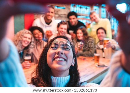 Happy friends taking a group selfie at pub - Group of multiracial millennial people having fun together at pub and taking a photo - Birthday party or after work meeting, happiness and teamwork concept #1532861198