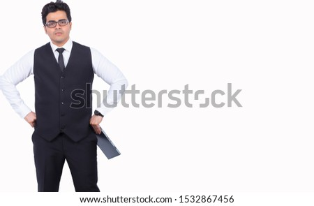 Handsome young businessman with digital tablet. Male professional is standing with hands on hips. He is wearing formals by copy space over white background. #1532867456