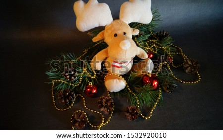 Christmas decoration with a plush deer among pine branches, cones and balls #1532920010