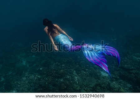 Young female free diver swims underwater in a colorful and sexy mermaid costume. #1532940698