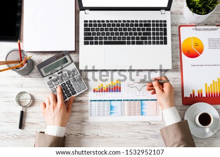 Businessman working at office desk with financial analytics. Top view office workplace with human hands calculating data. Flat lay table with laptop, calculator, business charts and cup of coffee. #1532952107
