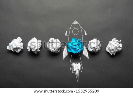 Rocket sketch drawing with crumpled blue paper ball on chalkboard. Successful business startup. Creative motivation with copy space. Unique business idea among failing ideas metaphor. Royalty-Free Stock Photo #1532955209