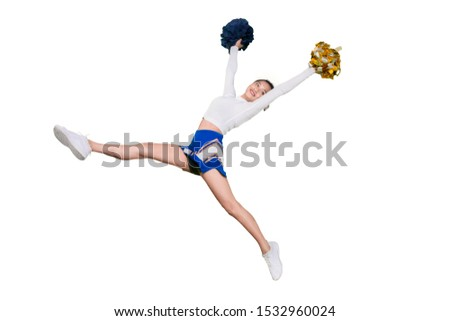 Picture of an excited cheerleader lifting pom poms while jumping in the studio