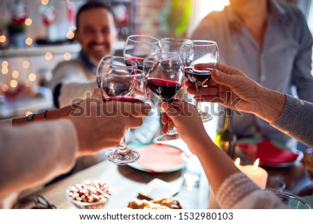 Family and friends dining at home celebrating christmas eve with traditional food and decoration, making a toast with best wishes with glass of wine #1532980103