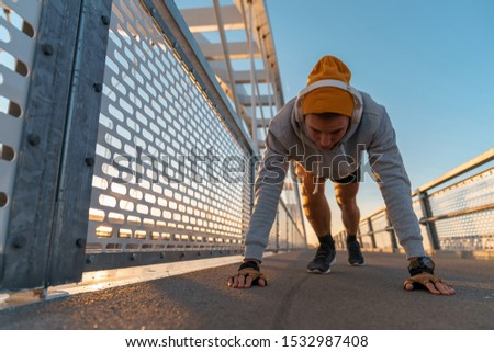 Young fitness male doing morning workout rutine on bridge outdoors. Healthy Lifestyle. Cardiovascular workouts - Stock Image #1532987408