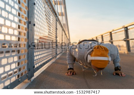 Young fitness male doing morning workout rutine on bridge outdoors. Healthy Lifestyle. Cardiovascular workouts. Push ups - Stock Image #1532987417