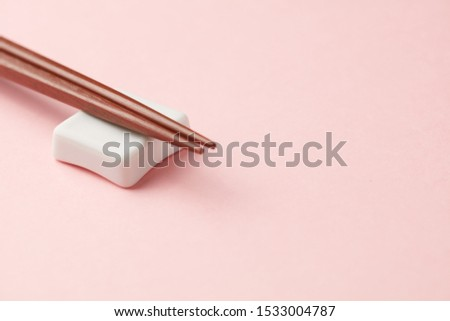 Wooden chopsticks and chopstick rest on bright paper background. Close up. Copy space.  #1533004787