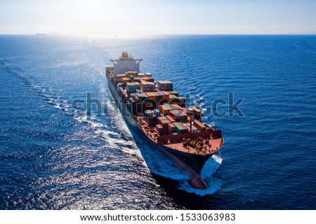 Aerial view of a heavy loaded container cargo vessel traveling in full speed over blue ocean Royalty-Free Stock Photo #1533063983