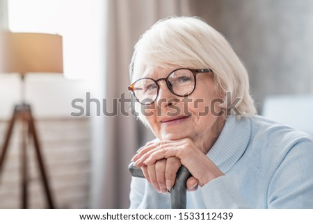 Close up of mature woman in glasses holding cane while sitting on sofa at home #1533112439