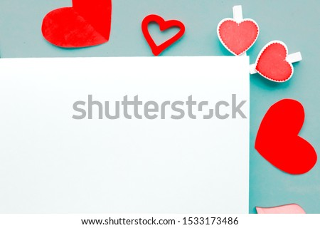 Red hearts and white blank on blue background - Valentine's Day greeting card #1533173486
