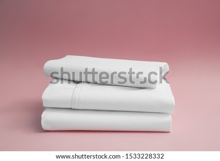 Stack of white bedding against pink backdrop, folded soft bed clothes, stack of white cotton sheets on a pink background for advertising, commercial and mock up Royalty-Free Stock Photo #1533228332