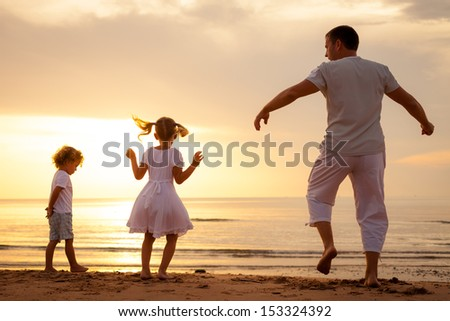 Happy beautiful family dancing on the  beach on the  dawn time. #153324392