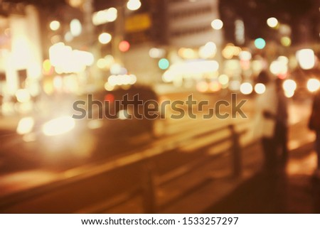 People walking at footpath in night time with light bokeh