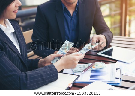 Businessmen are paying compensation to partners. or Businessmen are receiving dividends from investments. #1533328115