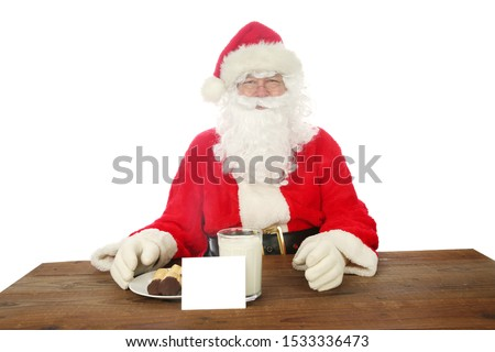 Santa Claus. Santa Claus aka Chris Kringle enjoys Cookies and Milk left for him one Christmas Eve. Isolated on white. Room for text.  #1533336473