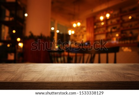 background Image of wooden table in front of abstract blurred restaurant lights #1533338129
