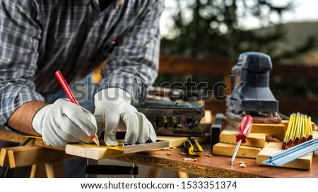 Adult carpenter craftsman wears protective leather gloves, with a pencil and the carpenter's square trace the cutting line on a wooden table. Construction industry, housework do it yourself. #1533351374
