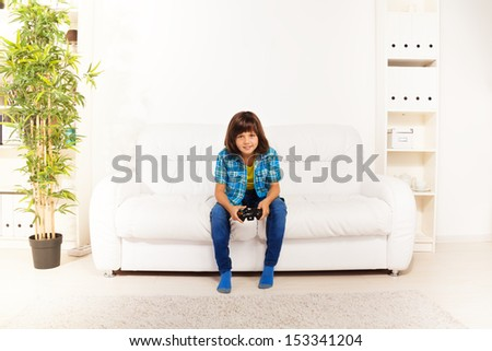 Happy 6 years old boy playing video games holding game controller sitting on the white coach in living room and looking at camera #153341204