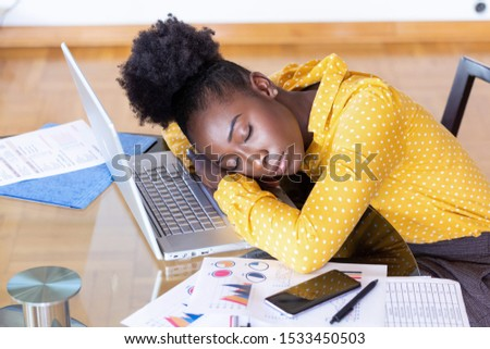 Tired overworked woman resting while she was working writing notes. Overworked and tired businesswoman sleeping over a laptop in a desk at home. Tired businesswoman #1533450503