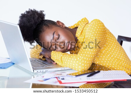 Tired overworked woman resting while she was working writing notes. Overworked and tired businesswoman sleeping over a laptop in a desk at home. Tired businesswoman #1533450512