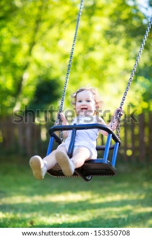 Adorable baby girl with big beautiful eyes and curly hair having fun on a swing ride at a playground in a sunny summer park #153350708