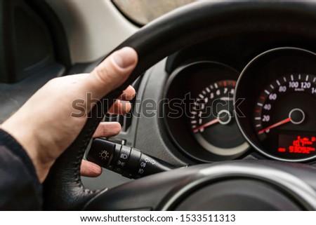 Driver's hand on steering wheel turns on turn signal #1533511313