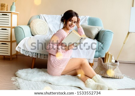 Beautiful girl on a cozy sofa in a light room with a cup of coffee. In a knitted pink sweater and knitted white socks. Christmas lights.cozy happy christmas. Lots of colorful bokeh lights. #1533552734