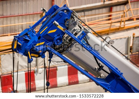 Blue crane boom with hooks and sling cable at construction site. Boom of mobile crane. #1533572228