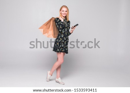 happy young woman holding shopping bags and mobile phone over white background #1533593411