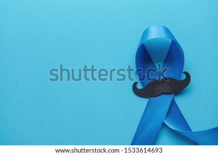 Light blue ribbons with mustache on blue background , Prostate Cancer Awareness, Movember November blue Men health awareness, International Men's Day #1533614693