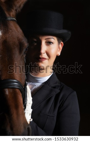 Young woman in tails in portraits next to her horse. She is holding her head next to the one of the horse and is looking into the camera. #1533630932